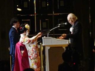 近藤学校長から卒業証書と専門士称号を授与される大阪ハイテクノロジー専門学校総代の﨑さんと、大阪保健福祉専門学校総代の今徳さん